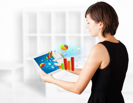 Young business woman looking at modern tablet with colourful diagrams Stock Photo - 16244684