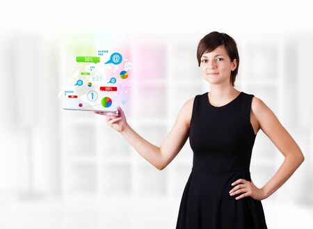 Young business woman looking at modern tablet with colourful technology icons Stock Photo - 16242683