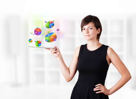 Young business woman looking at modern tablet with colourful pie charts Stock Photo - 16242704