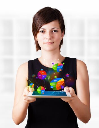 Young business woman looking at modern tablet with colourful pie charts Stock Photo - 16245562