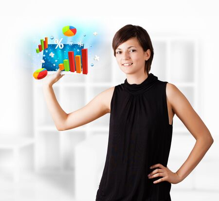 Young business woman looking at modern tablet with colourful diagrams photo