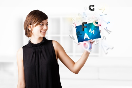 woman tablet: Young business woman looking at modern tablet with alphabet