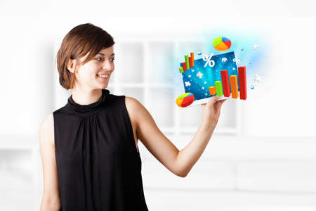 Young business woman looking at modern tablet with colourful diagrams Stock Photo - 16290507
