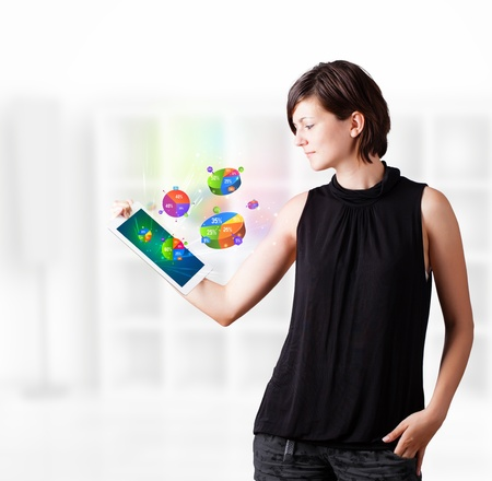 woman tablet: Young business woman looking at modern tablet with colourful pie charts Stock Photo