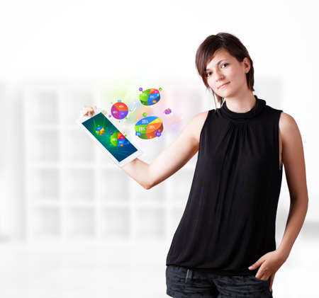 Young business woman looking at modern tablet with colourful pie charts Stock Photo - 16243066