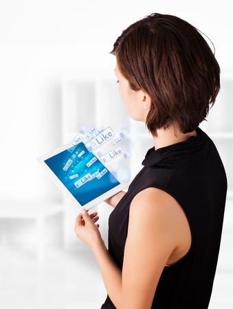 trabajo social: Mujer de negocios joven mirando tableta moderno con iconos sociales Foto de archivo
