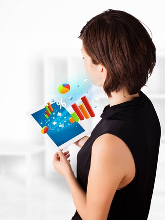 Young business woman looking at modern tablet with colourful diagrams Stock Photo - 16290864