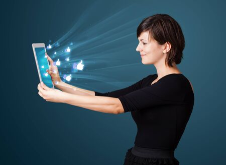 Young business woman looking at modern tablet with abstract lights and social icons Stock Photo - 16242959