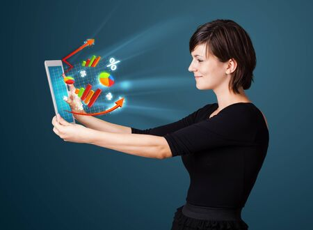 Young business woman looking at modern tablet with abstract lights and various diagrams Stock Photo - 16243050