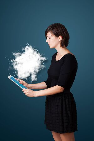 Young business woman looking at modern tablet with abstract cloud photo