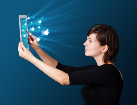 woman tablet: Young business woman looking at modern tablet with abstract lights and social icons
