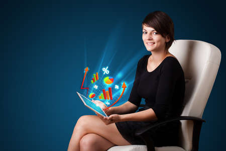 Young business woman looking at modern tablet with abstract lights and various diagrams photo