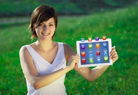 tablet pc in hand: Young business woman looking at modern tablet with abstract lights and various icons