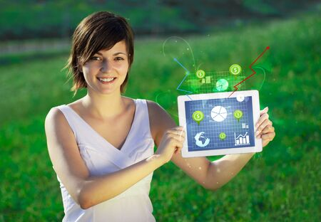 Young business woman looking at modern tablet with abstract light and various diagrams photo