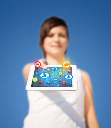 Young business woman looking at modern tablet with abstract lights and social icons photo