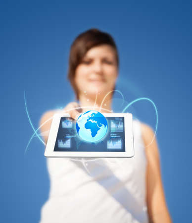 Young business woman looking at modern tablet with abstract lights and globe photo