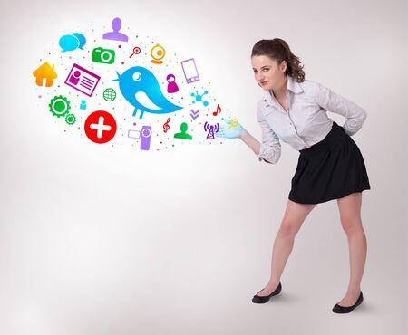 trabajo social: Mujer de negocios joven que presenta coloridos iconos sociales sobre fondo brillante Foto de archivo