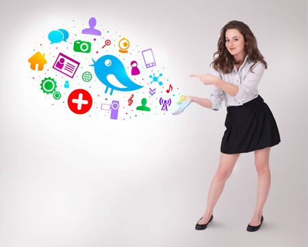 Young business woman presenting colourful social icons on bright background photo
