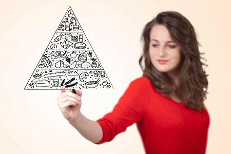 Young woman drawing a various food pyramid on whiteboard  photo
