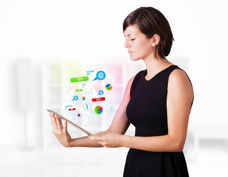 Young business woman looking at modern tablet with colourful technology icons Stock Photo - 16367843