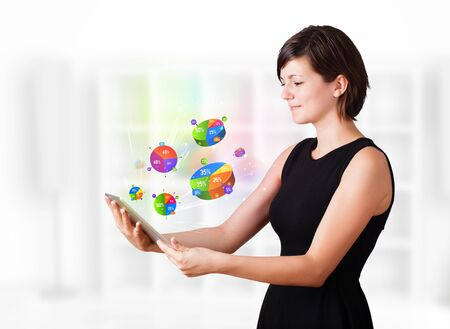 Young business woman looking at modern tablet with colourful pie charts Stock Photo - 16367812