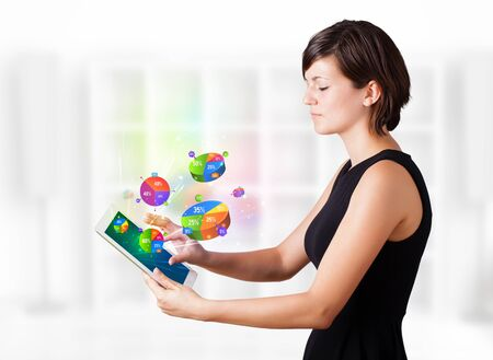 Young business woman looking at modern tablet with colourful pie charts Stock Photo - 16367822