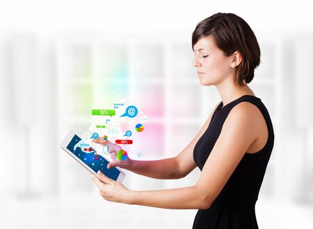 Young business woman looking at modern tablet with colourful technology icons Stock Photo - 16367819