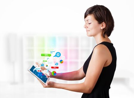 Young business woman looking at modern tablet with colourful technology icons Stock Photo - 16367851