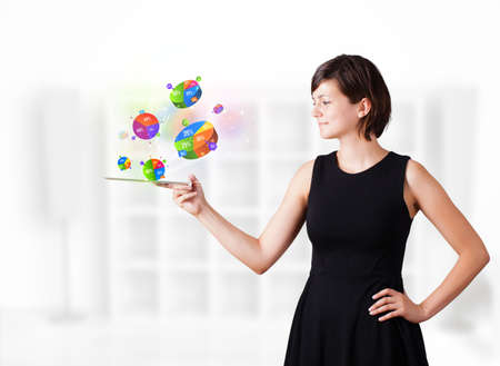 Young business woman looking at modern tablet with colourful pie charts Stock Photo - 16367833