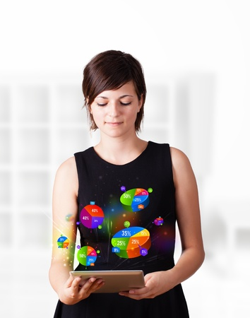 marketing plan: Young business woman looking at modern tablet with colourful pie charts Stock Photo