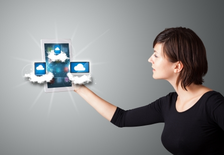 tablet pc in hand: Beautiful young woman holding tablet with modern devices in clouds