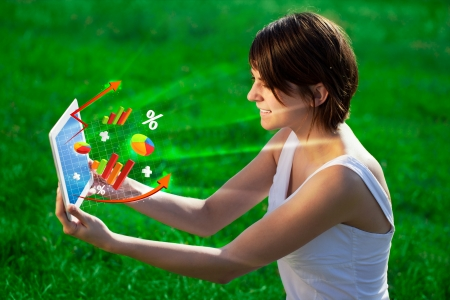 tablet pc in hand: Young business woman looking at modern tablet with abstract light and various diagrams