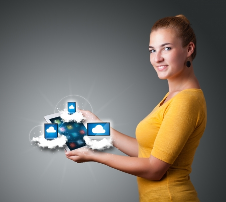 Beautiful young woman holding tablet with modern devices in clouds Stock Photo - 16523942