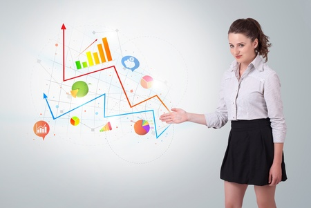 Young business woman presenting colorful charts and diagrams on bright background   photo