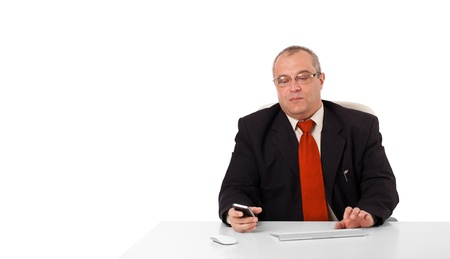 copys pace: businessman sitting at desk and holding a mobilephone with copys pace, isolated on white Stock Photo
