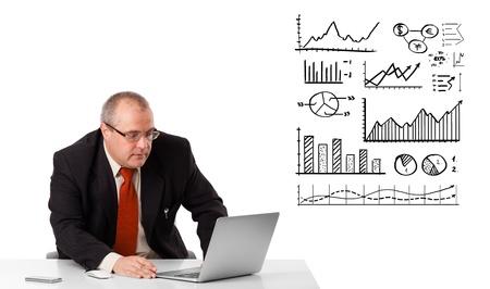 statistique: Homme d'affaires assis � un bureau avec des diagrammes et des portables, isol� sur blanc Banque d'images