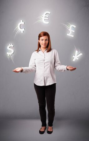 pretty young lady standing and juggling with currency icons photo
