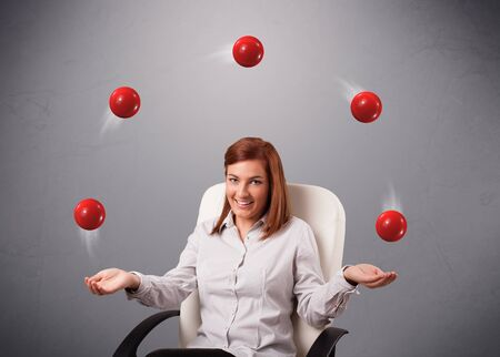 pretty young girl sitting and juggling with red balls photo