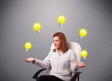 beautiful young lady sitting and juggling with light bulbs photo