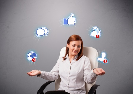 attractive young woman sitting and juggling with social network icons photo