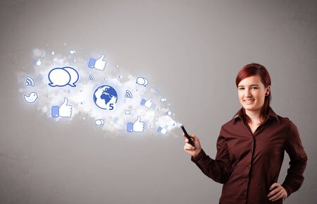 Pretty young girl holding a phone with social media icons in abstract cloud Stock Photo - 16638892