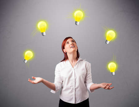 beautiful young lady standing and juggling with light bulbs photo