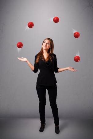 pretty young girl standing and juggling with red balls photo