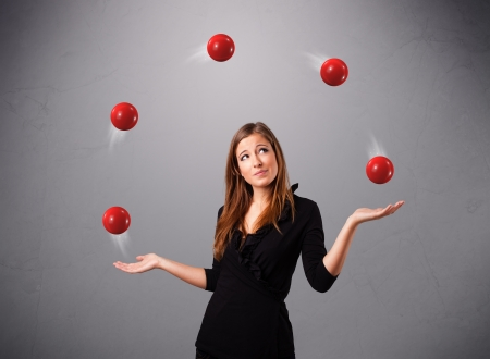 hard working woman: pretty young girl standing and juggling with red balls