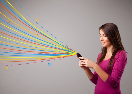 Happy young girl holding a phone with colorful abstract lines photo