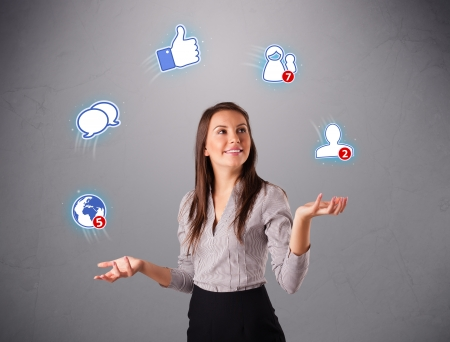 attractive young woman standing and juggling with social network icons Stock Photo