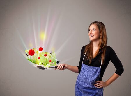Beautiful young woman cooking fresh vegetables with abstract lights Stock Photo - 16973089