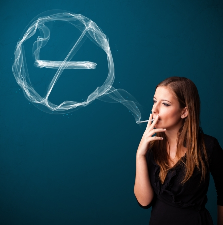 women smoking: Pretty young lady smoking unheathy cigarette with no smoking sign Stock Photo