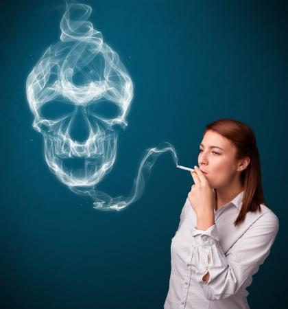 Pretty young woman smoking dangerous cigarette with toxic skull smoke Stock Photo - 16746733