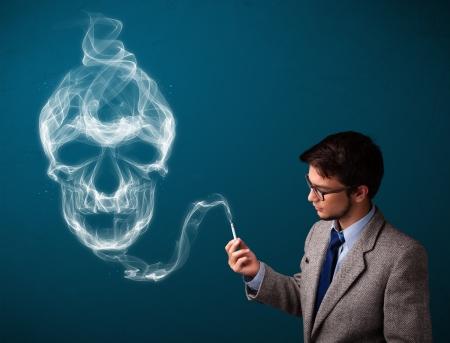dangerous man: Handsome young man smoking dangerous cigarette with toxic skull smoke Stock Photo